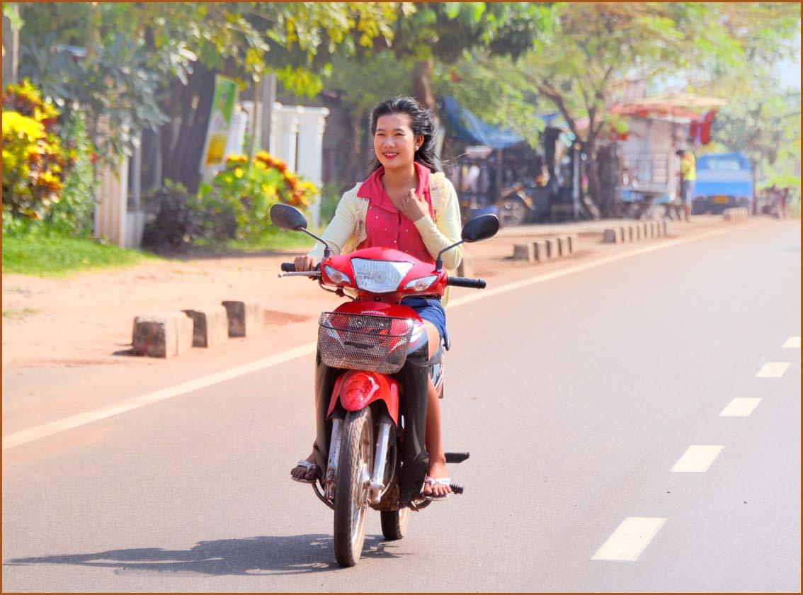 000_さっそうとスクーターで走るラオスのお嬢さん